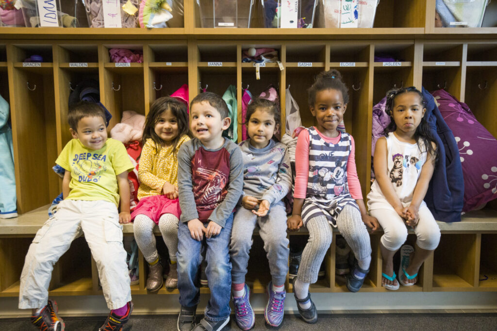 Diverse children sitting on a bench
